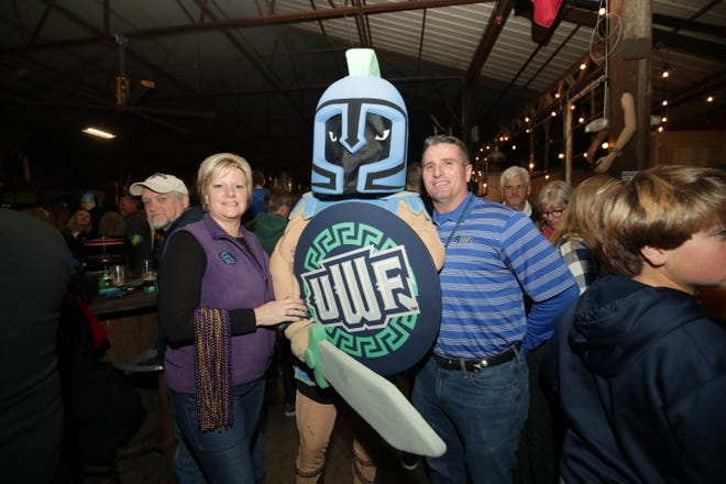 Christine Wilson (left) and Kevin Wilson (right) pose with the University of West Florida mascot at a pep rally prior to Saturday's NCAA Division II National Championship. Christine, a Minnesota State alum, and Kevin, a UWF alum, have had a divided house over the national championship.