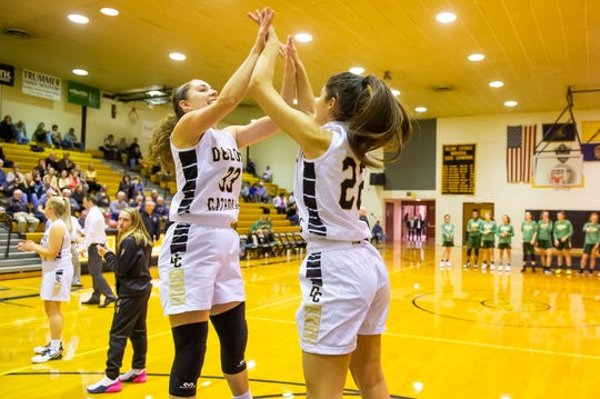 Delone Catholic's Makenna Mummert (22) high-fives Maddie Sieg during the starting lineup introductions prior to a YAIAA Division III game against York Catholic Friday, Dec. 20, 2019. The Squirettes won, 61-32.
