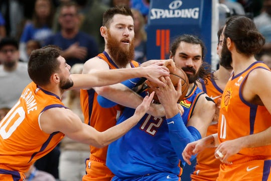 Oklahoma City Thunder center Steven Adams (12) fights for the ball with Phoenix Suns guard Ty Jerome (10) and center Aron Baynes, second from left, during the second half of an NBA basketball game Friday, Dec. 20, 2019, in Oklahoma City. (AP Photo/Sue Ogrocki)