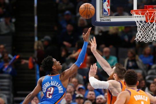 Oklahoma City Thunder guard Shai Gilgeous-Alexander (2) shoots in front of Phoenix Suns center Aron Baynes, center, during the second half of an NBA basketball game Friday, Dec. 20, 2019, in Oklahoma City. (AP Photo/Sue Ogrocki)