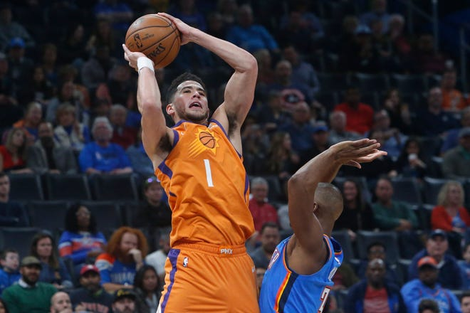 Phoenix Suns guard Devin Booker (1) shoots over Oklahoma City Thunder guard Chris Paul during the second half of an NBA basketball game Friday, Dec. 20, 2019, in Oklahoma City. (AP Photo/Sue Ogrocki)