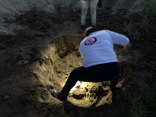 A volunteer with the Searching Mothers of Sonora continues digging up dirt from a pit where they located a buried body west of Hermosillo, Mexico on Dec. 3, 2019.