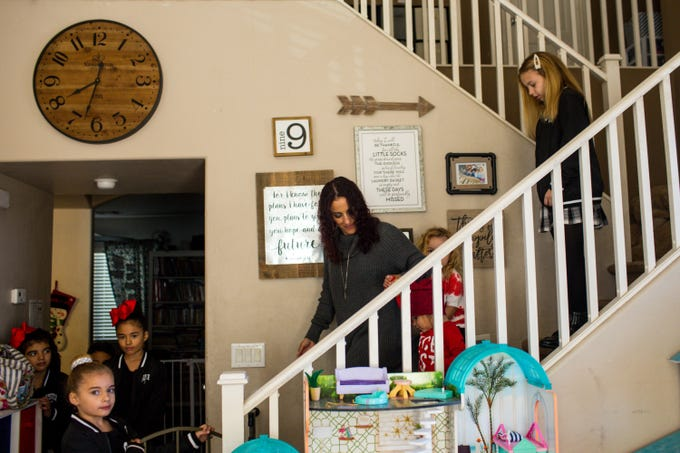 Sara Lopez brings her and Justin Lopez's seven children downstairs to meet Santa, his elves and the 100 Club of Arizona Friday, December 20, 2019 in Goodyear. Justin Lopez is a Peoria firefighter and was injured last April when an APS battery exploded.
