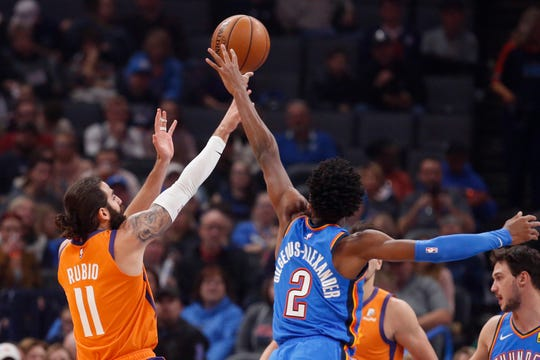 Phoenix Suns guard Ricky Rubio (11) shoots next to Oklahoma City Thunder guard Shai Gilgeous-Alexander (2) during the first half of an NBA basketball game Friday, Dec. 20, 2019, in Oklahoma City. (AP Photo/Sue Ogrocki)