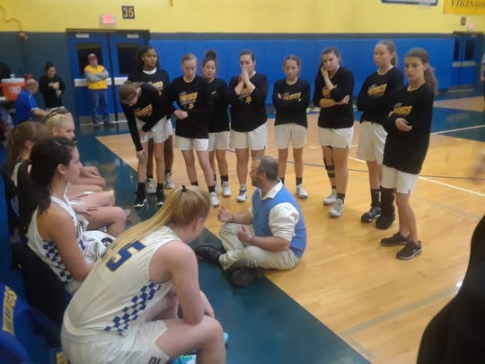 Northern Lebanon coach Ken Battistelli takes a seat on the floor to speak to his team during a timeout Friday night.