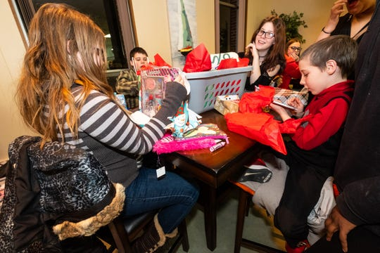 From left, siblings Mattalynn Eagle, 11, Nathanial Gray, 15, Mandy Gray, 16, and Ashton Eagle, 11, open gifts donated to them by Difference Makers during a Christmas party Friday, Dec. 20, 2019, at The Center of Port Huron.