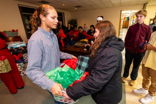 KC Cureton, 15, left, hands a basket of gifts to Patti Landini during a Christmas party Friday, Dec. 20, 2019, at The Center of Port Huron. Landini and her children were one of the families adopted that were given gifts by Difference Makers.