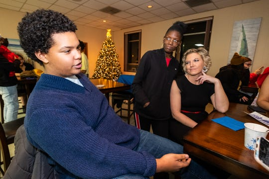 Jasmine Woods, 17, center, and Meggan Mertz, right, listen while Henry Bush, 15, tells his story during a Christmas party for Difference Makers Friday, Dec. 20, 2019, at The Center of Port Huron.