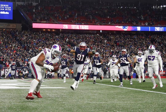 Buffalo Bills offensive tackle Dion Dawkins (73) catches a touchdown pass as New England Patriots defensive end Deatrich Wise (91) defends during the second quarter at Gillette Stadium.