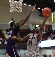 Iona Prep's Keeshawn Jones (11) goes up as New Rochelle's Amani Parkes (10) defends in the opening round of the Slam Dunk Basketball Tournament at the Westchester County Center in White Plains on Saturday, December 21, 2019.