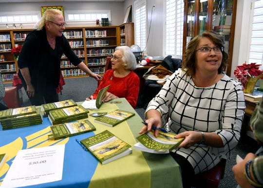 "Jewellee Kuenstler (right) signs a copy of her book for a customer as Susan Siewert Waller speaks with Amelia Perry (seated) Tuesday at the Shackelford County Library. Kuenstler is the editor for ""Heavy Date Over Germany: The Life and Times of B-17 Tail Gunner Ray Perry."""