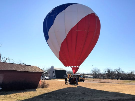 A hot air balloon landed in a small lot between South First and Second streets Sunday morning. It wasn't an emergency but to change personnel. Its chase bus is parked on the street. The balloon quickly rose back into the sky and headed north across Abilene.