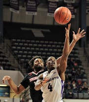 ACU's Damiel Daniels (4) drives to the basket as Nicholls player defends in the first half. ACU beat the Colonels 79-61 in the Southland Conference game Saturday, Dec. 21, 2019, at Moody Coliseum.