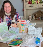 Rebecca Smayda displays some of the items that have already been collected for layettes – clothing, toiletries and other items for babies. She is the founder of the Christ Child Society of Greater Binghamton, which helps to improve the lives of children.