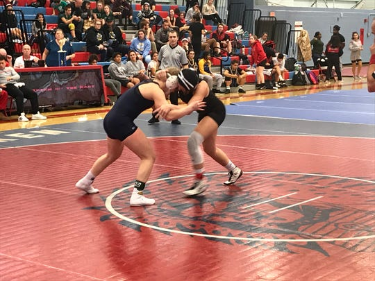 Overbrook's Alexis Rosano (left) locks up with Kingsway's Alexa Firestone in the 143-pound final of Sunday's Queen of the East Tournament  at Pennsauken High School.