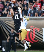 Cincinnati Bearcats wide receiver Alec Pierce (12) catches a pass as UCLA Bruins defensive back Elijah Gates (12) defends in the first quarter of an NCAA football game, Thursday, Aug. 29, 2019, at Nippert Stadium in Cincinnati.