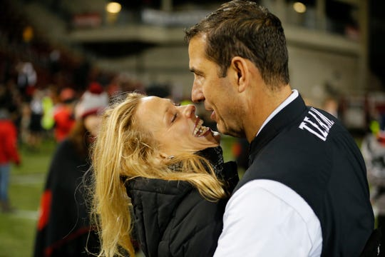 Cincinnati Bearcats head coach Luke Fickell gets a hug and kiss from his wife Amy after the final play of the fourth quarter of the NCAA American Athletic Conference game between the Cincinnati Bearcats and the Temple Owls at Nippert Stadium in Cincinnati on Saturday, Nov. 23, 2019. The Bearcats clinched the AAC East championship with a 15-13 win over Temple.