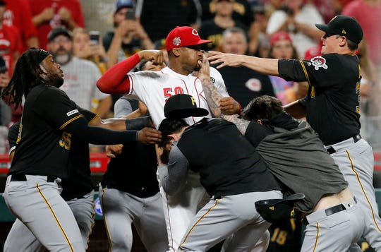 Cincinnati Reds relief pitcher Amir Garrett (50) throws punches as he is held back by a number of Pittsburgh Pirates players as a bench clearing brawl breaks out in the ninth inning of the MLB National League game between the Cincinnati Reds and the Pittsburgh Pirates at Great American Ball Park in downtown Cincinnati on Tuesday, July 30, 2019. The Pirates won 11-4.