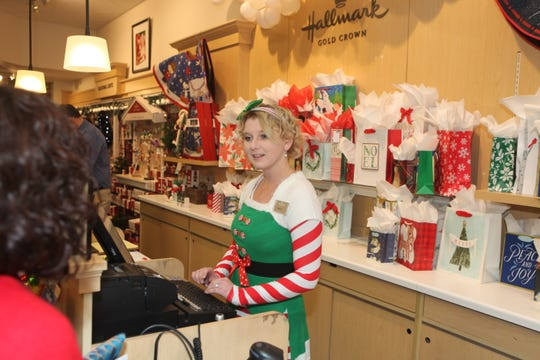 Madison Boren helps a customer during the final weekend of Christmas shopping at Governor's Square Mall on Saturday, Dec. 21, 2019.