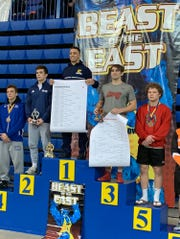John Poznanski stands atop the podium at the Beast of the East after winning the 182-pound title