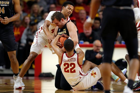 Iowa State guards Rasir Bolton, top, and Tyrese Haliburton, bottom, try to wrestle the ball away from Purdue Fort Wayne forward Matt Holba, center, during the first half of an NCAA college basketball game, Sunday, Dec. 22, 2019, in Ames, Iowa. (AP Photo/Matthew Putney)