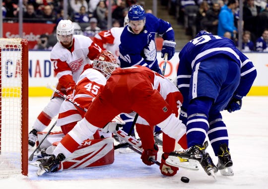 Detroit Red Wings goaltender Jonathan Bernier (45) watches the puck while teammate Brendan Perlini (29) tries to keep Toronto Maple Leafs center John Tavares (91) away from it during first-period NHL hockey game action in Toronto, Saturday, Dec. 21, 2019.