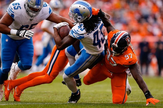 Lions running back Bo Scarbrough is tackled by Broncos linebacker Jeremiah Attaochu, right, and cornerback Isaac Yiadom in the first quarter on Sunday, Dec. 22, 2019, in Denver.