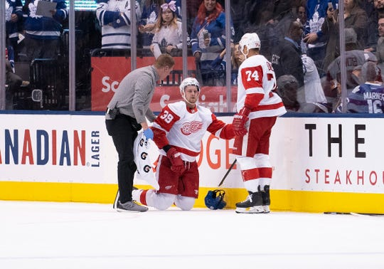 Detroit Red Wings right wing Anthony Mantha (39) is helped up off the ice by the team trainer during the third period against the Toronto Maple Leafs at Scotiabank Arena.