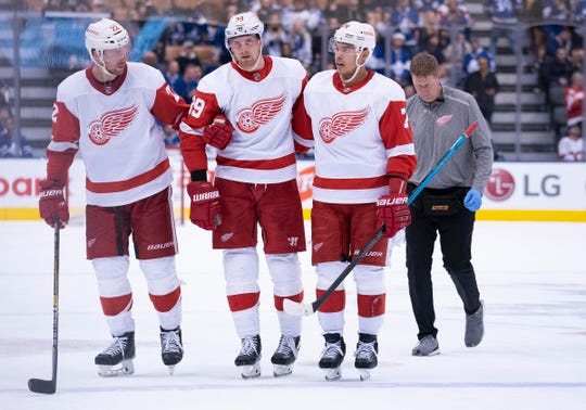 Detroit Red Wings right wing Anthony Mantha (39) is escorted off the ice by Detroit Red Wings defenseman Patrik Nemeth (22) and Detroit Red Wings defenseman Madison Bowey (74) during the third period against the Toronto Maple Leafs at Scotiabank Arena.