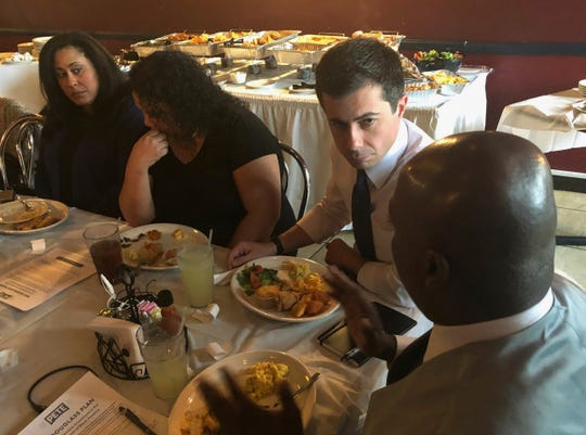 Democratic presidential candidate Pete Buttigieg, third from left, listens to Mikey Kelly as the South Bend mayor meets with black voters at a soul food restaurant in North Las Vegas, Saturday, Dec. 21, 2019.