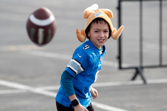 A Detroit Lions fan plays football outside Empower Field in Denver before Sunday's game.