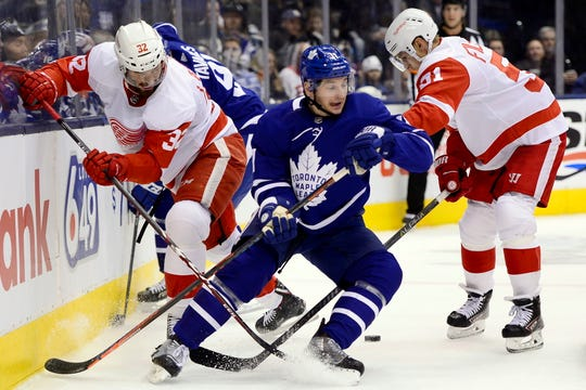 Detroit Red Wings defenseman Brian Lashoff (32) and teammate Valtteri Filppula (51) vie for control of the puck with Maple Leafs left wing Zach Hyman.