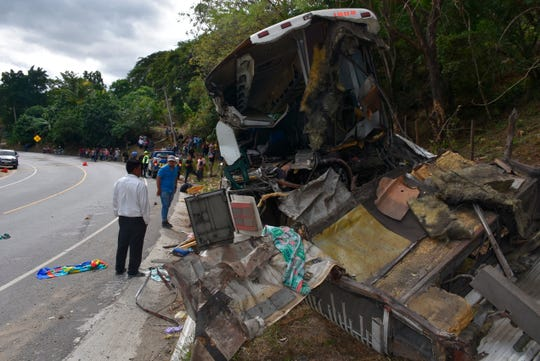 The wreckage of a passenger bus that crashed with a trailer truck lays on the side of the highway in Gualan, Guatemala, Saturday, Dec. 21, 2019
