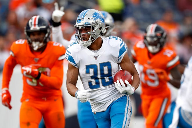 The Lions' Jamal Agnew runs a punt return back for a 64-yard touchdown against the Broncos.