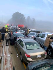 Drivers and emergency personnel remain on the scene of a multi-vehicle pileup on Interstate 64 in York County, Va., Sunday, Dec. 22, 2019.