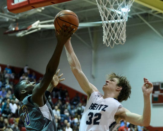 Christian Brothers College's Chevalier Brenson (0) and Reitz's Ethan Higgs (32) fight for the ball during the Bosse Winter Classic Shootout at Bosse High School in Evansville, Saturday, Dec. 21, 2019. The CBC Cadets defeated the Panthers, 78-72.