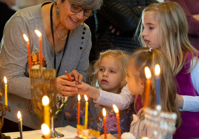 Gloria Mazo, Sunday school principal at Temple Adath B'Nai Israel, helps Maren Pellett, 8, upper right, with the shammash, or helper candle, as she lights the first candle on her family's menorah in celebration of Hanukkah Sunday morning, Dec. 22, 2019. Also pictured are Lillian Pellett, 4, center, and Elle Laborwit, 5, bottom right.