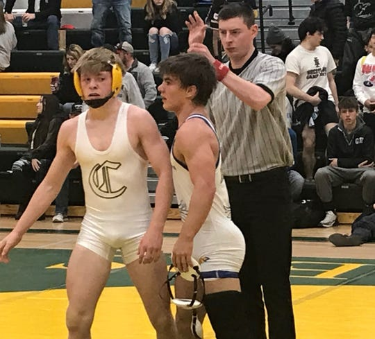 Cooper Birdwell (center) of Fergus High gets his hand raised as Helena Capital's Carson DesRosier walks away following Birdwell's 6-3 decision in the 132 lb. championship at the CMR Holiday Classic Saturday. The win was the 100th of Birdwell's career.