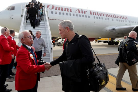 """Kirk Ferentz is welcomed by a line of """"Red Coats,"""" the hospitality group at the Holiday Bowl, on Saturday at the San Diego Airport. This is Ferentz's third Holiday Bowl but first since 1987 and first as Iowa's head coach."""