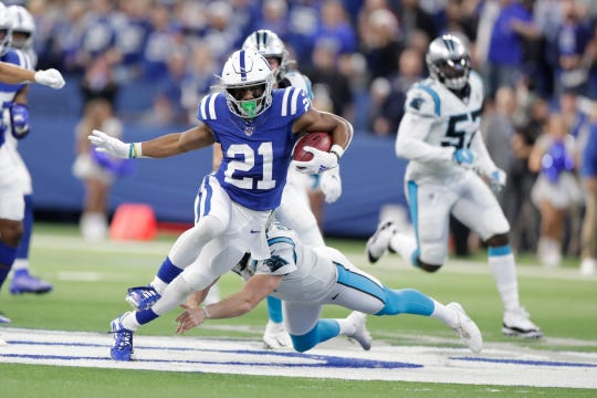 Indianapolis Colts' Nyheim Hines (21) runs past Carolina Panthers punter Michael Palardy (5) during the first half of an NFL football game, Sunday, Dec. 22, 2019, in Indianapolis.