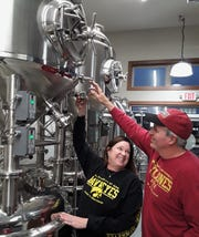 Lisa Corrin prepares to taste a batch of craft beer prepared by her husband Cal at the new House Divided Brewery in Ely. The name comes from the owners' friendly Iowa-Iowa State rivalry as noted by their sweatshirts.