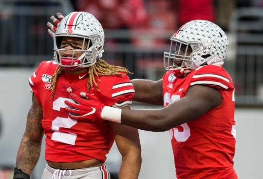Ohio State defensive end Zach Harrison congratulates fellow end Chase Young for his sacks against Wisconsin