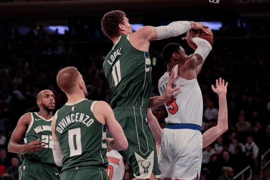 Bucks center Brook Lopez gets his hand on the ball as RJ Barrett of the Knicks tries to pass to a teammate in the first quarter.