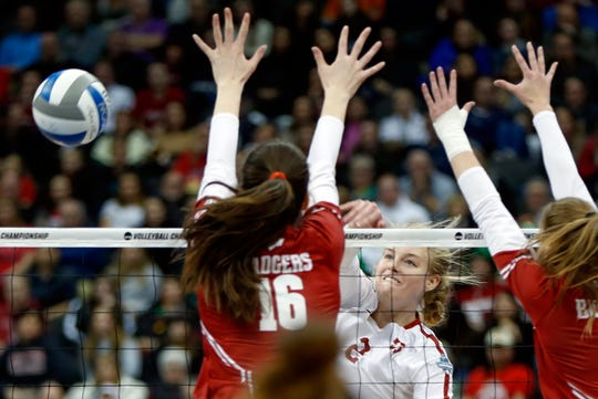 Stanford's Kathryn Plummer spikes around the block by Wisconsin's Dana Rettke during the NCAA Division I women's volleyball championship match Saturday night.