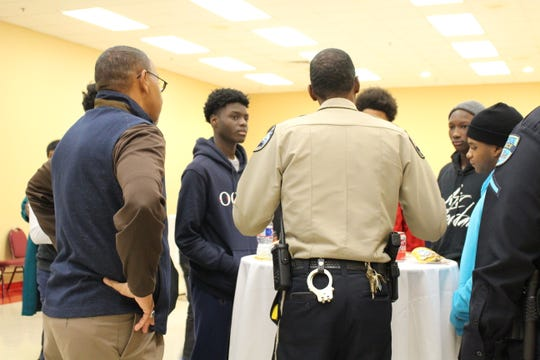 Teens at the SAVE program open house were able to connect and speak with leaders of SAVE and other youth-focused initiatives at the city and parish level. During the event, several gathered around a table to speak with officers and deputies.