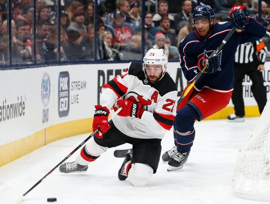 New Jersey Devils' Kyle Palmieri, left, keeps the puck away from Columbus Blue Jackets' Seth Jones during the first period of an NHL hockey game Saturday, Dec. 21, 2019, in Columbus, Ohio.