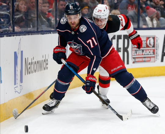 Columbus Blue Jackets' Nick Foligno, front, tries to clear the puck as New Jersey Devils' Blake Coleman defends during the first period of an NHL hockey game Saturday, Dec. 21, 2019, in Columbus, Ohio.