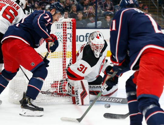 New Jersey Devils' Gilles Senn, center, of Switzerland, makes a save between Columbus Blue Jackets' Nick Foligno, left, and Kevin Stenlund, of Sweden, during the second period of an NHL hockey game, Saturday, Dec. 21, 2019, in Columbus, Ohio.