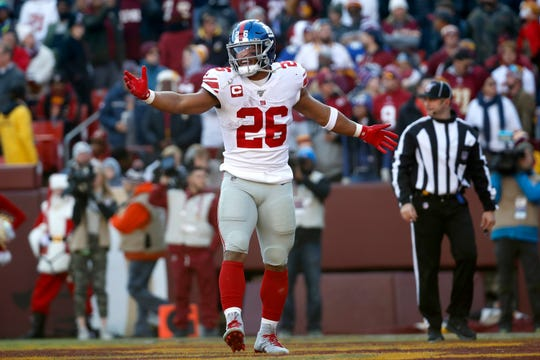 New York Giants running back Saquon Barkley reacts after catching a touchdown pass from quarterback Daniel Jones during the first half of an NFL football game against the Washington Redskins, Sunday, Dec. 22, 2019, in Landover, Md. (AP Photo/Alex Brandon)