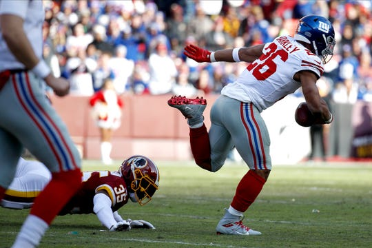 New York Giants running back Saquon Barkley, right, runs for a long touchdown while avoiding a tackle from Washington Redskins free safety Montae Nicholson during the first half of an NFL football game, Sunday, Dec. 22, 2019, in Landover, Md. (AP Photo/Patrick Semansky)